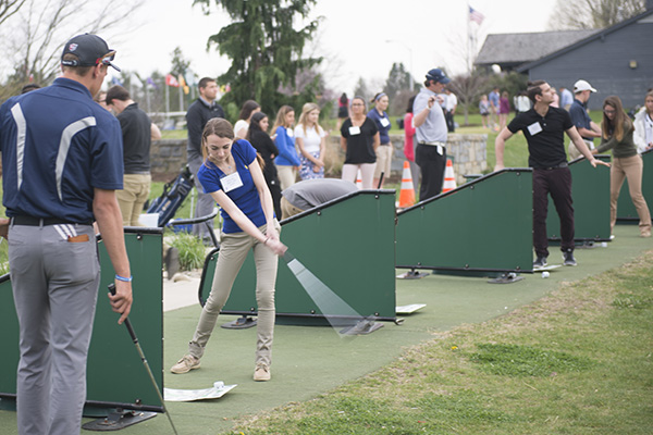 Students swings golf club during golf practice