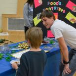 Student teaching elementary student about nutritional science.