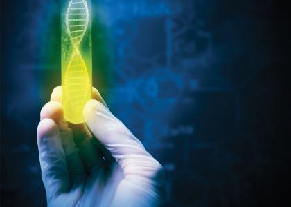A gloved hand holding a green and yellow test tube with a DNA graphic inside on a dark background.