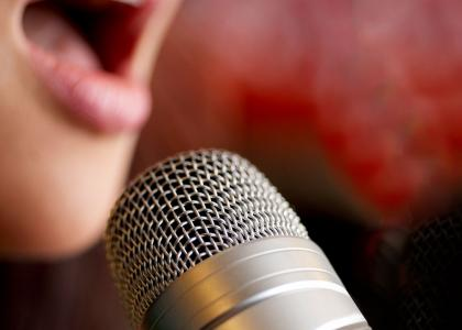 Close up of a woman singing into a microphone. Red and black background