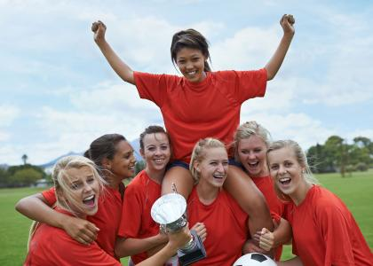 Women's sports team in a huddle, holding a trophy and raising a teammate on their shoulders.