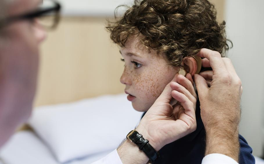 A doctor is fitting a hearing aid in a young child.