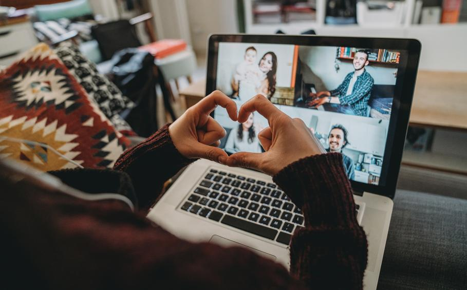 Person holding their hands in the shape of a heart during a video conference with family and friends.