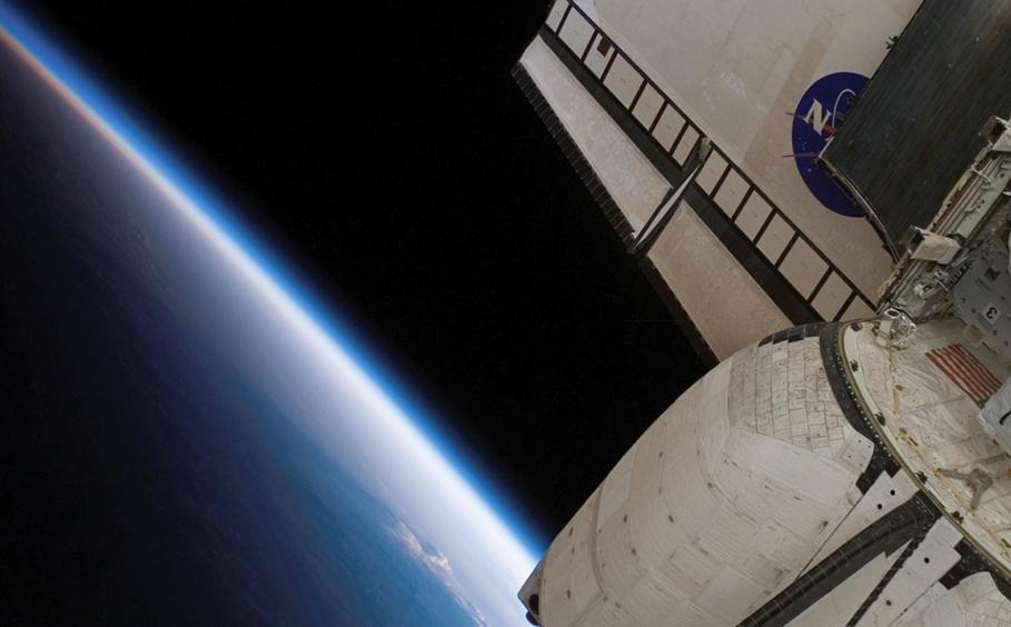 Close up of the backend of a space shuttle with a section of the earth in the background.
