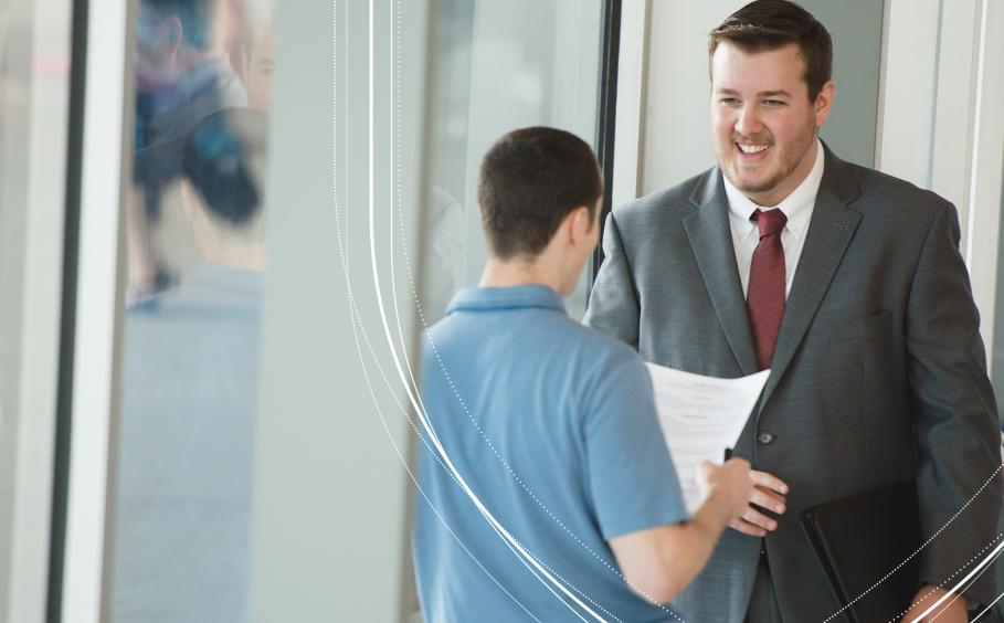Student wearing a suit in a conversation in a job setting.