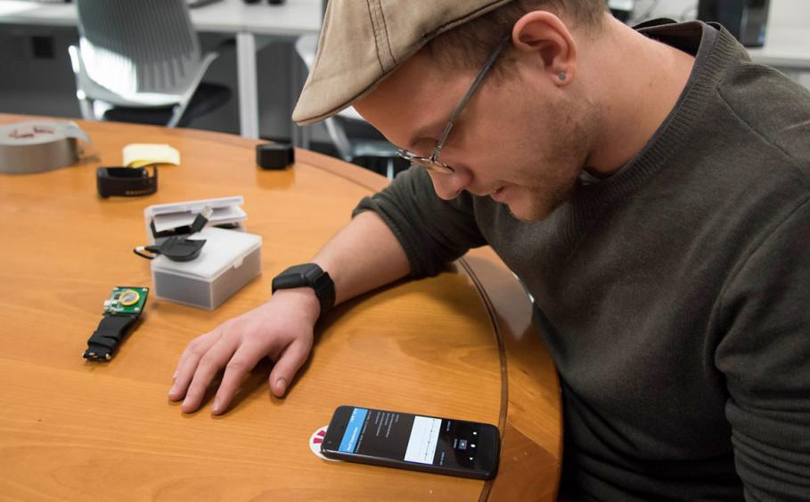 Graduate student working on pairing the watch device with a smart phone.