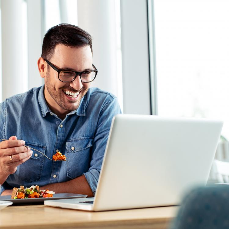 Man eating lunch at computer